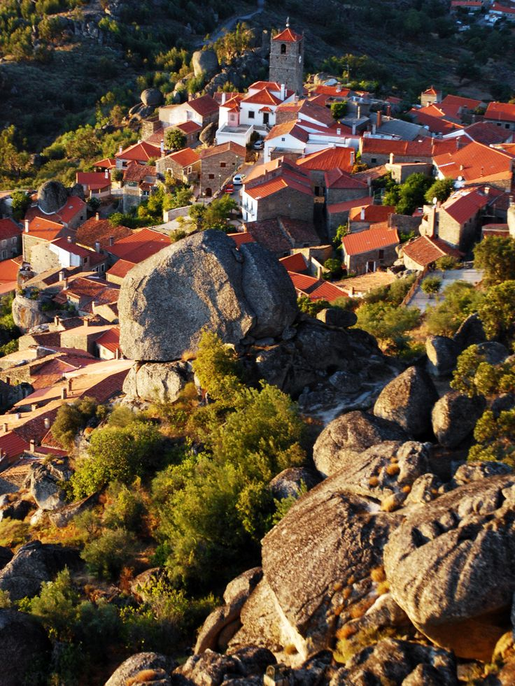 """Monsanto is a beautiful Portuguese village built on the side of a mountain. Local houses are squeezed between huge boulders and narrow streets are carved from the rock. It was named """"the most Portuguese village in Portugal"""" in 1938."""