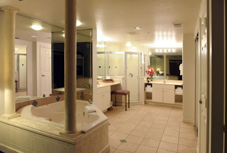 Large bathroom with jacuzzi tub among columns.  2 vanities each with traditional dressing room lighting.