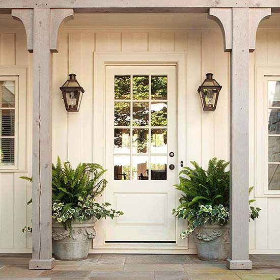 This wood-and-glass door nearly fades into the background as it's painted the same ivory hue as the rest of the house and could easily be mistaken for a window. But, wall-mounted lanterns and mammoth plant pots hint at the front door's location./