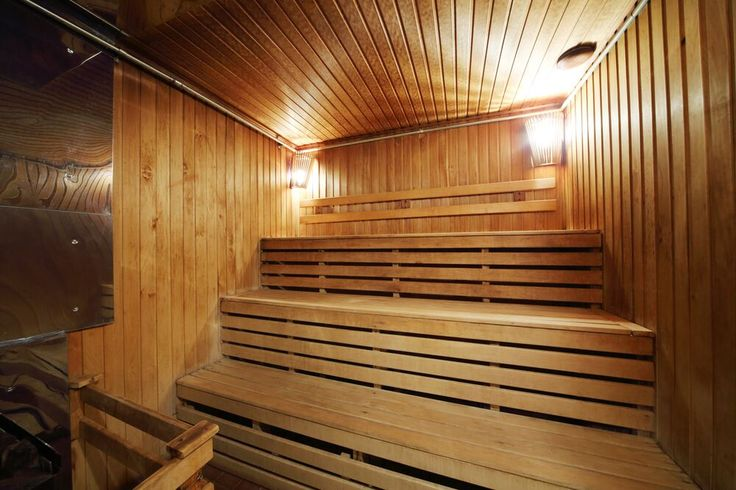 This sauna is equipped to hold a large amount of people, with benches stacked on top of each other. Light wood paneling forms both the benches and the walls.