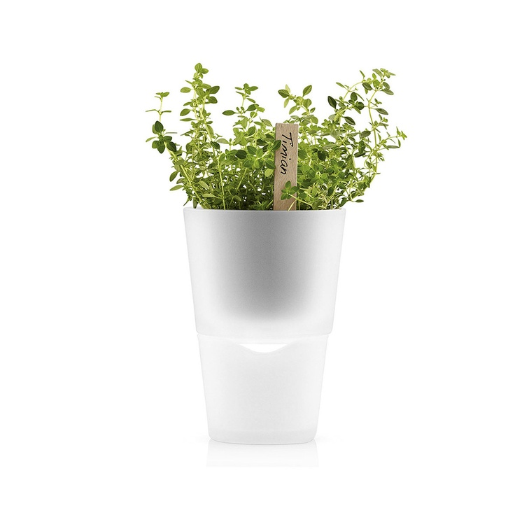 "Self-Watering Herb Pot - a smart container that nurtures your mint or basil with minimal maintenance. The two-piece pot includes a top portion with nylon ""roots"" that enable plants to suck water from a lower reservoir. When you leave for summer vacation there's no need to worry about your flowers—just fill the bottom with some H20 and go."