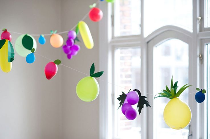 "Blow up balloons to different sizes and attach ""leaves"" to create a colorful, fruit-themed garland."