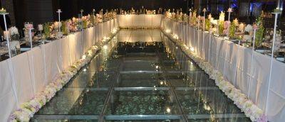 Tavolo imperiale intorno alla piscina per un matrimonio in spiaggia dalle tinte parigine.