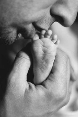 Es una fotografía que representa la realidad donde un padre besa el pie de su bebe.