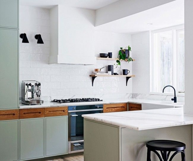 A bright kitchen with marble countertops, feminine design with a sorbet palette that goes beautifully with the masculine black and timber details. Design by Arent & Pyke. Caption: Marble, light green kitchen, black details.