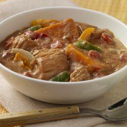 Mantequilla de cacahuete, sabrosos tomates y pimientos dulces en combinación con pollo y boniato para una comida de cocción lenta con influencia africana