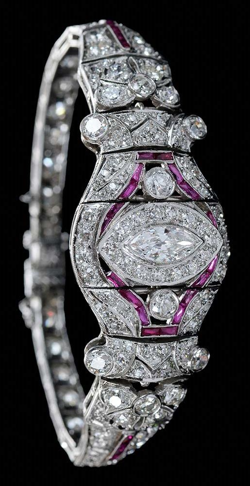An Art Deco platinum, diamond and synthetic ruby bracelet. Centring one marquise brilliant cut diamond, with 130 Old European, single and round full-cut diamonds, estimated combined diamond weight 10 carats, accented with 28 rectangular mixed-cut synthetic rubies.