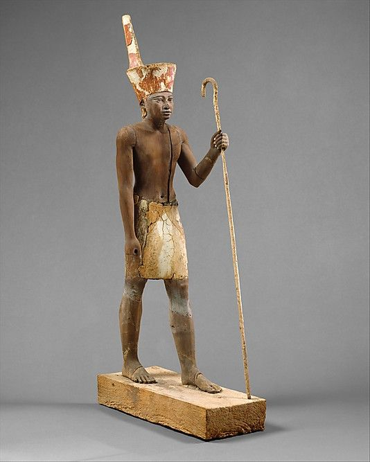 Ancient Egypt during the Middle Kingdom, 1919-1878 B.C. Statue located at the Metropolitan Museum of Art. Clothing and accessories: Red crown of Lower Egypt, schenti, holding a crook of god Anedjti