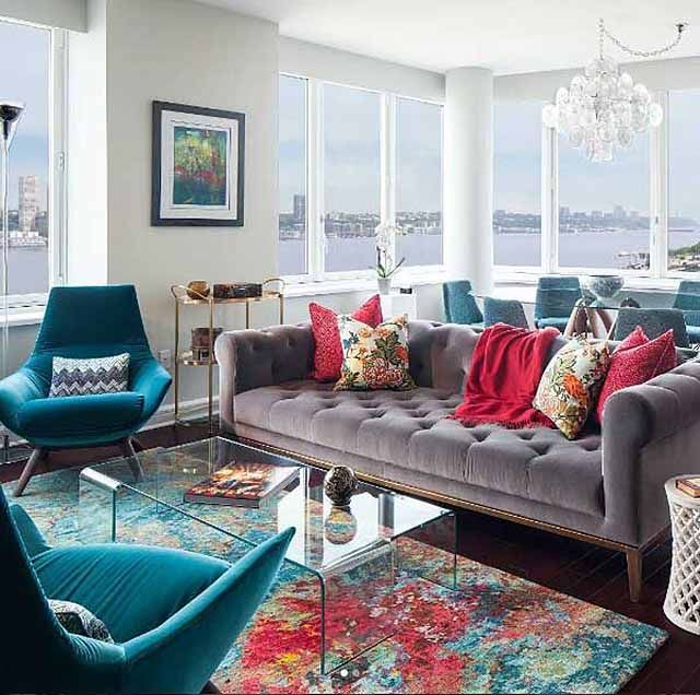 A vibrant living space using the colorful Atlantis Aqua. A sofa is a muted mauve velvet with deep and patterned cushions. There also two accompanying armchairs in teal velvet. The coffee table is all glass and the carpet has deep red and teal hues in an abstract design. A dining room is also partially visible in the background