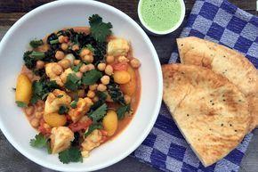 Heerlijk Indiaas getint recept voor een vegetarische korma curry met bloemkool, aardappels, kikkererwten, palmkool en koriander-raita met naanbrood. Lekker!