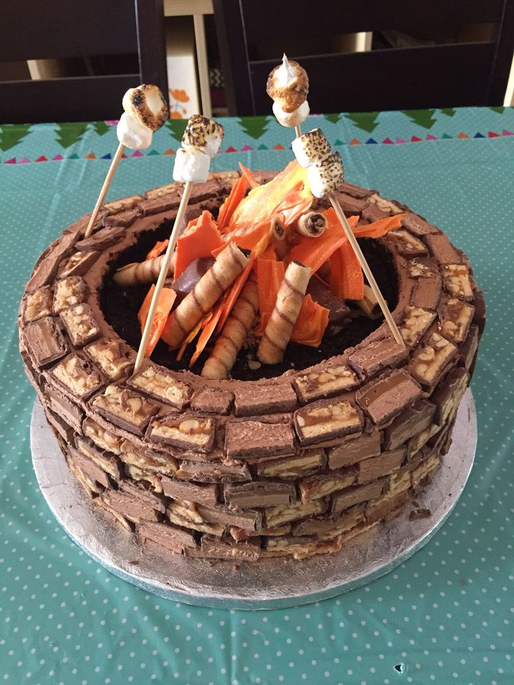 Campfire cake, Firepit cake, Camping cake, roasting marshmallows, Glamping cake. The sides are sliced candy bars, the fire is colored white chocolate.