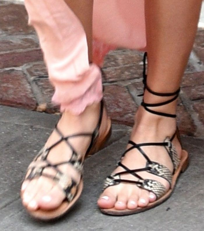 Margot Robbie showing off her feet in lace-up flat sandals