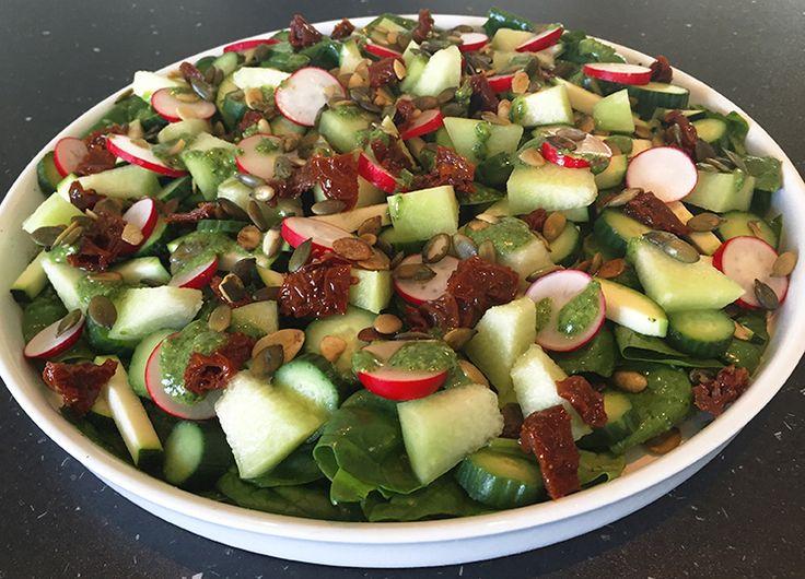 Spændende og forfriskende melonsalat med frisk spinat, squash, agurk, radiser, soltørret tomat, ristede græskarkerner og grøn pesto dressing.