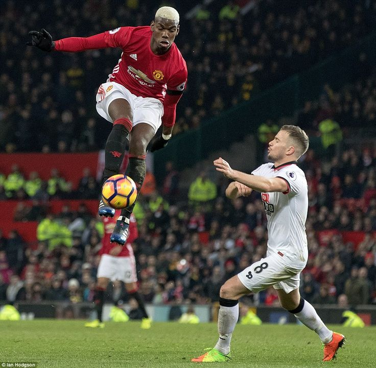 Paul Pogba leaps into the air to control the ball ahead of former United player Tom Cleverley at Old Trafford