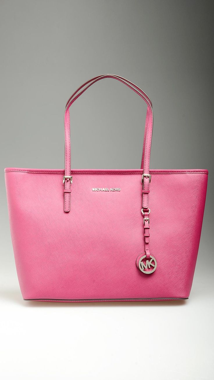 Fuxia Saffiano leather Jet Set Travel shopping bag featuring top zip, buckled handles, monogram lining, four inner open pockets and a zippered one,  protective studs, silver hardware, logoed medallion at front, 14'' x 5.9'' x 10.2'', 100% Saffiano leather.