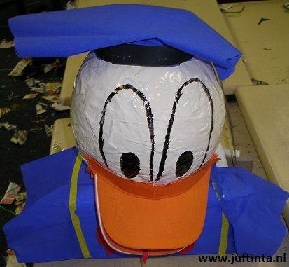 Is deze Donald Duck suprisee niet geweldig? Eerst is het hoofd gemaakt van papier maché. Toen deze droog was, is het hoofd met de onderkant vastgezet op een doos. De doos wordt zijn matrozenpak. Op het hoofd natuurlijk nog het matrozenmutsje. Tenslotte is van twee zonnekleps de snavel gemaakt.