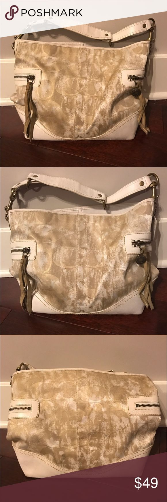 Coach Signature Hobo Bag Gold with Coach signature print. White leather accents and zipper and tassel details on each side. Shoulder strap and hook closure. Zipper pocket inside with 2 additional pockets. Shows some minor signs of use and has some marks on bottom leather and corners but overall good condition. Coach Bags