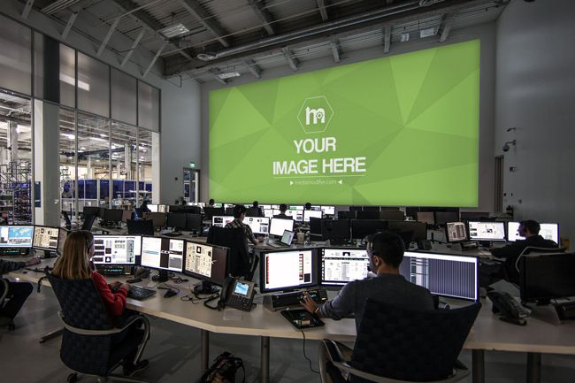 a large space center control room with people working on their computers and a large projector screen displayed on the