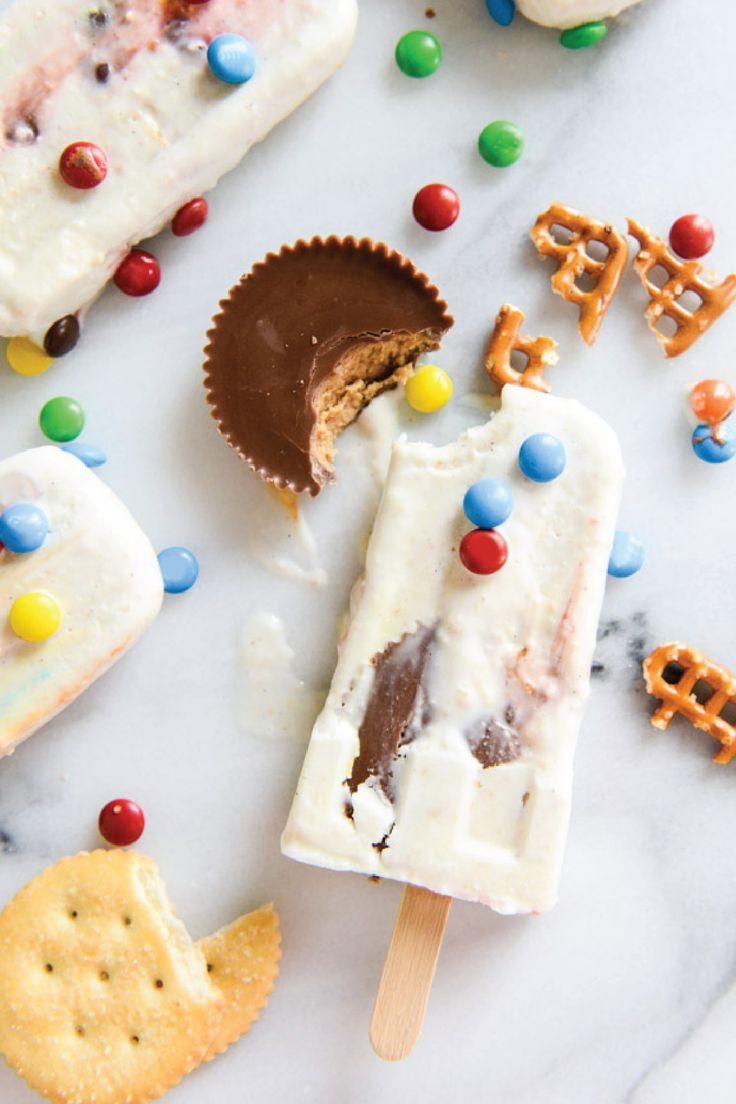 Wondering what this recipe for Late Night Snacksicles entails? Simply combine creamy ice cream with your favorite sweet treats—like pretzels, chocolate covered candies, and peanut butter bites!