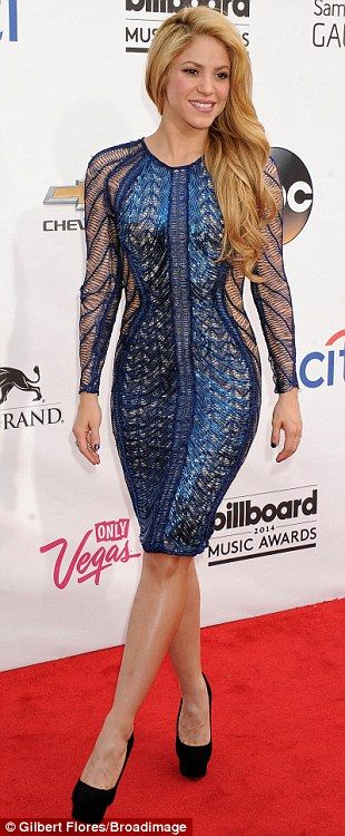 Her hips don't lie! The Colombian beauty Shakira accentuated her slim physique in a stunning bright blue draped knee-length frock with sheer side panels and long sleeves that featured an optical illusion shape on the front, while she added height to her petite frame with black platform stilettos, her golden complexion complemented by her long tumbling curls
