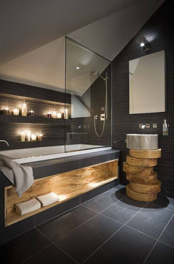 The combination of dark color with light wood creates a calming environment in this bathroom.
