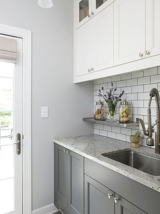 Clean & Polished Opposite the washer and dryer, a wall of painted cabinets and a granite countertop put the polish on this petite laundry room. A floating stainless-steel shelf mounted to the backsplash introduces a spot to stow soaps and fresh flowers.