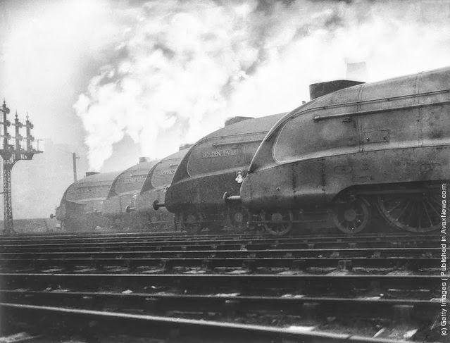 A row of LNER streamlined locomotives belch out smoke at a London railway station, where they are to be tested out. From the left, they ar...