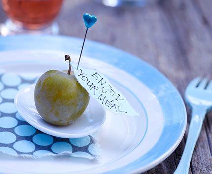 Wir haben Renekloden verwendet, aber auch anderes Obst - wie Pflaumen oder kleine Äpfel - eignet sich für die liebevolle Deko. Aus farbigem, etwas dickerem Papier reißen Sie per Hand Stückchen heraus, die in ihrer Form an Blätter erinnern. Jedes Blatt können Sie beschriften: mit dem Motto des Abends, einem Willkommensgruß oder dem Namen jedes Gastes. Das Blatt pinnen Sie mit der hübschen Dekonadel nahe des Stiels ins Obst. Herznadeln von Rice bei Michaelsen - Scandinavian Living