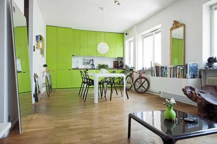Den grønne kjøkkeninnredningen bryter med hvite vegger og tak, og er et friskt pust i rommet. Selve innredningen består av store glatte flater, uten dørhanker.