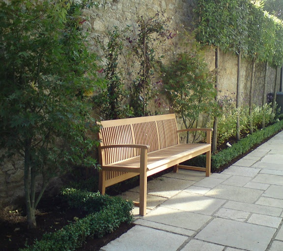 Pleached Carpinus used to soften extremely high granite wall