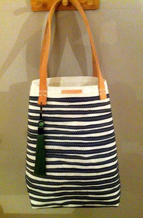 Large open Upcycled sail cloth tote <br>Large open tote with hand cut individual strips of slate leather front and bottom paneling. <br>The interior of this tote is in it's natural state, finished with a small pocket for items such as keys, phone etcs.<br>Tan leather straps have been used for the hand...