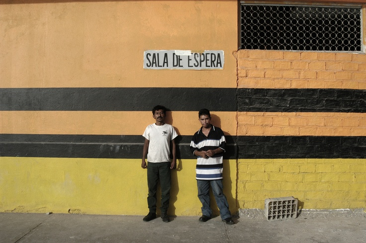 """Two migrants wait behind a train depot outside Tapachula, southern Mexico.  After nightfall, they'll try to jump a north-bound freighter - one of the so-called """"death trains"""" - in their quest to reach the U.S."""