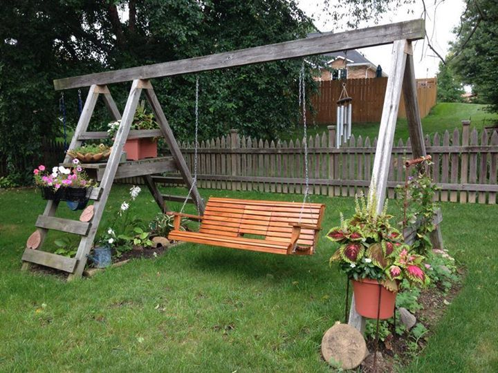"Diana Daily says, ""This is what my daughter did with their kids old swing set. If you click and enlarge this you can see the detail on each side."" First, a swing set, now a conversation spot,...then,....rockin' the grandbabies? We LOVE this, Diana,...all surrounded with flowers! - Flea Market Gardening on FB"