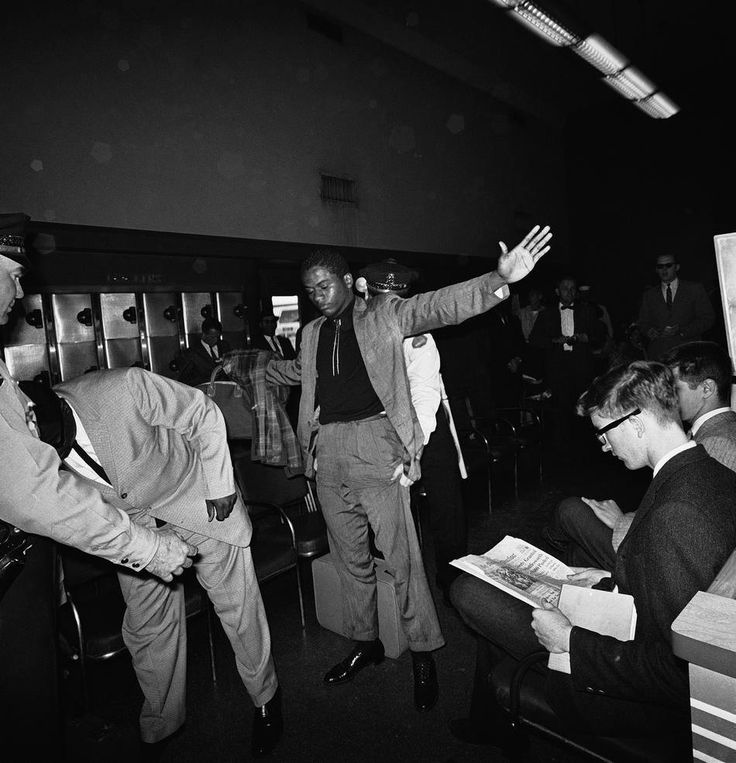 Местные полицейские в Монтгомери, штат Алабама под надуманным предлогом обыскивают чернокожих пассажиров с автобусных рейсов всадников свободы в зале ожидания автовокзала, который до недавнего времени предназначался только для белых ... (1961 год)