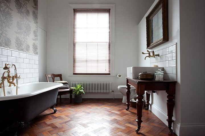 "Homes: Wigan house - bathroom  In the bathroom, Timorous Beasties' Thistle wallpaper was the starting point for the design. ""I saw the wallpaper in a bar in Manchester and based the rest of the room on it. The look I was going for is rough luxe."" The sink sits on a table that was a junk shop find; Bev found the taps on eBay. ""They're from an old hospital."""