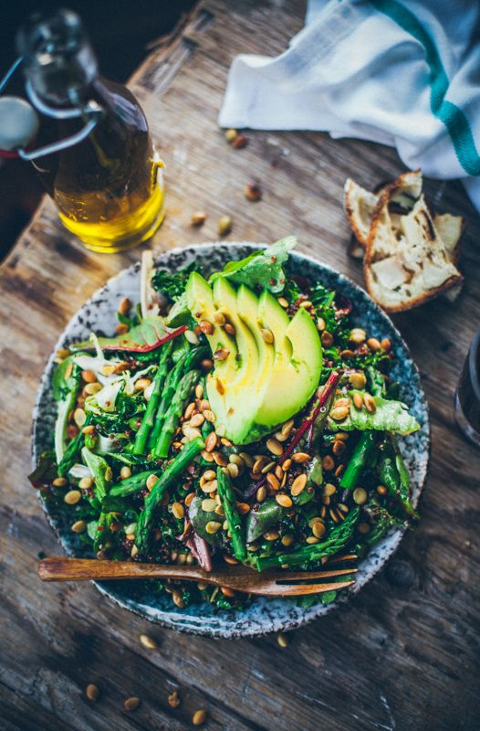 Kale salad with quinoa, avocado, asparagus and sunflower seeds.