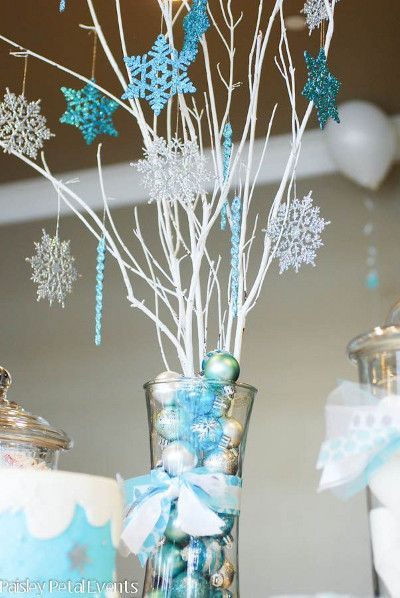 Using holiday ornaments and white sticks for centerpieces at Frozen party