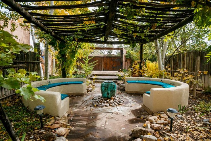 Garden Seating Area Sink into the natural beauty and breathtaking beauty of this Southwestern outdoor lounge. A natural wood pergola shades the bright turquoise cushions of the curved sofas. Plant life grows right into the structures, enriching the space.