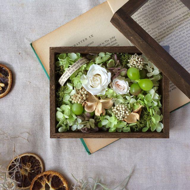 ダークブラウンに塗り込んだラスティック風の木箱。グリーンをベースに、小花、木の実などをたくさん詰め込んだ、ナチュラルなフラワーボックスです。蓋を開けて楽しむもよし、閉じて楽しむもよし。。。小さな宝箱のようなお花を楽しんでいただけたらと思います。※木箱の蓋...