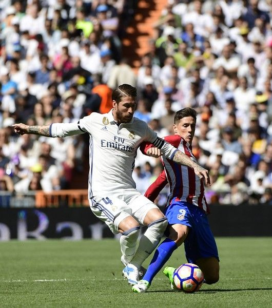 Real Madrid's defender Sergio Ramos (L) vies with Atletico Madrid's forward Fernando Torres during the Spanish league football match Real Madrid CF vs Club Atletico de Madrid at the Santiago Bernabeu stadium in Madrid on April, 8, 2017. / AFP PHOTO / PIERRE-PHILIPPE MARCOU