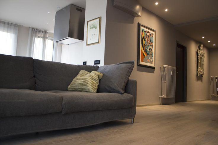 Divano in tessuto dalle tonalità del grigio scuro, pavimento in legno, color delle pareti tortora