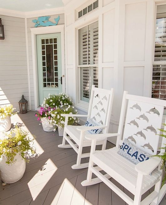 Coastal Porch with Dolphin Cutout Rocking Chairs and Mermaid Wall Art.... http://www.completely-coastal.com/2017/03/beach-house-in-white-turquoise-coral.html