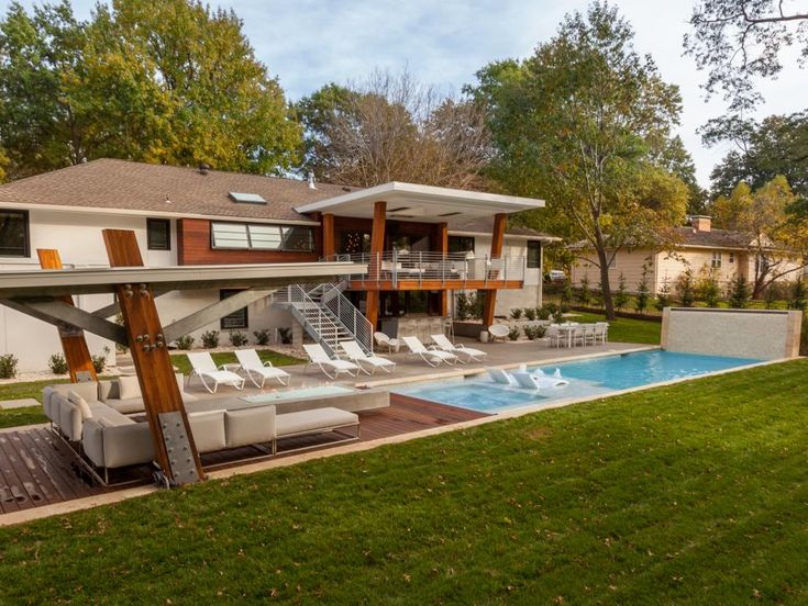 A trimmed lawn works well in this midcentury modern-inspired yard, helping to accentuate the space's clean lines. A covered lounge and bar provide shade during the day, without drawing attention from the pool or brilliant light displays.