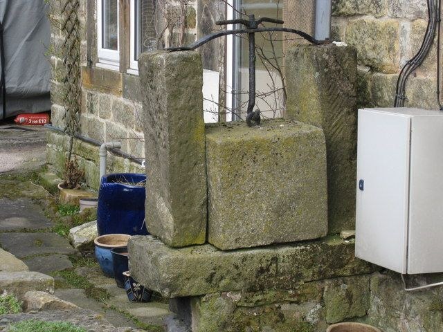 A stone cheese press attached to side of building.