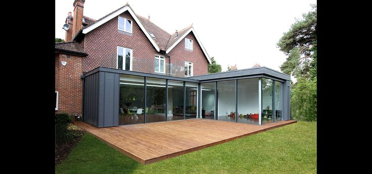 A L shaped extension using IQ's sliding glass doors and frameless glass balustrades above for an invisible roof terrace showing the doors closed