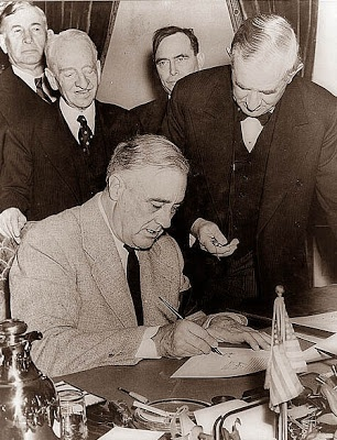 This photograph shows President Franklin Roosevelt signing the Declaration of War against Japan, which he did on this date, December 8, 1941. This occurred after Japan's surprise attack on Pearl Harbor.