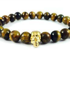 Dizarro to męska biżuteria najwyższej jakości produkowana z kamieni półszlachetnych, srebra, złota oraz kryształów Swarovski™.  Bransoletka wykonana z kamieni 'tygrysiego oka' oraz czaszki pokrytej 23-karatowym, złotem. Szczegóły:- czaszka pokryta 23-karatowym, włoskim złotem- bransoletka wkładana na elastycznej gumce- średnica kulek: 8 mm- bransoletka zapakowana w eleganckie, czarne pudełko