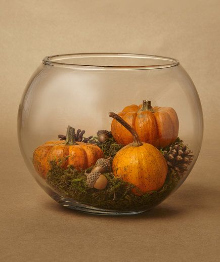 You can turn a few mini pumpkins, pinecones, acorns, and moss into a classy terrarium centerpiece. It's perfect for fall.