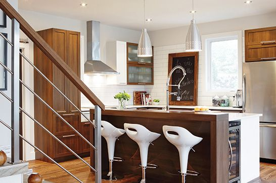 Vue de la cuisine sur l'îlot, les tabourets blancs, les armoires de bois, les luminaires et les éléments en inox.