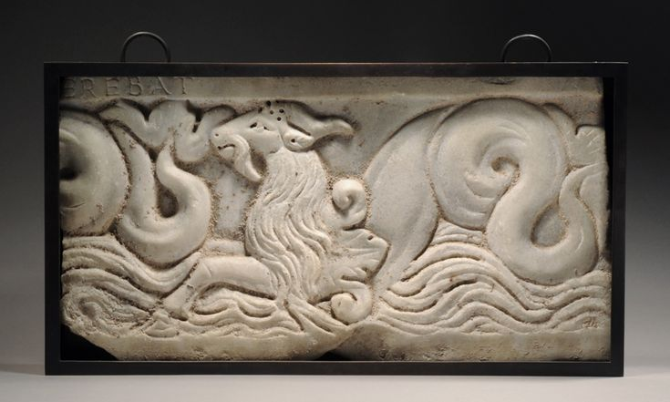 ROMAN MARBLE RELIEF SECTION DEPICTING A CAPRICORN,    A mythical animal with the foreparts of a goat and the body and tail of a fish. From a sarcophagus; a partial inscription remaining: EREBAT.      Late 2nd Century AD: Mythical Animal